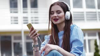 Beautiful stylish woman listens to music on her cell-phone with headphones, closes her eyes, and sings along, gestures emotionally. Music fan, being happy. Stylish look, red lips, accessories.