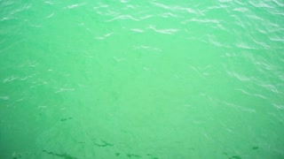 Beautiful surface of green water for background. Ripples and wave close-ups in a super slow motion view from above