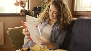 Beautiful teenage girl with long curly hair at home sitting on couch, holding notebook, studying.