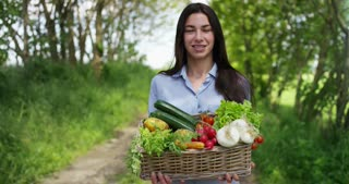 Beautiful young girl holding a basket of vegetables, in the background of nature. Concept: biology, bio products, bio ecology, grow vegetables, natural pure and fresh product, vegetarians, healthy.