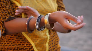 Beautiful young gypsy afro black woman corrects bracelet. Boho jewelry on hands. Girl in gold dress showing bohemian accessories outdoor. Slow motion. Femininity concept