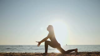 Beautiful young woman practicing morning yoga on sand sea beach. Surya Namaskar - Sun Greetings. Slow motion