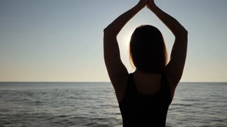 Beautiful young woman practicing morning yoga on sand sea beach. Surya Namaskar - Sun Salutation. Slow motion