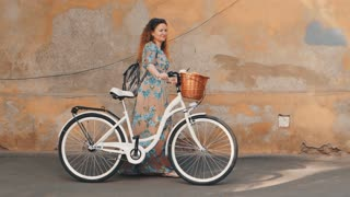 Beautiful young woman with blonde curly hair wearing long dress walking the old street near retro white bicycle with basket. Slow Motion