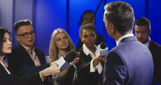 Big group of multiracial journalists with microphones and other technological equipment having interview with middle-aged politician in underlit studio