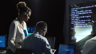 Black and white woman and man monitoring in dark room of space mission control center. Outer works of astronauts. Elements of this image furnished by NASA