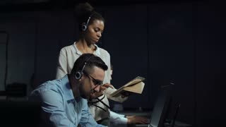 Black and white woman and man monitoring in dark room of space mission control center