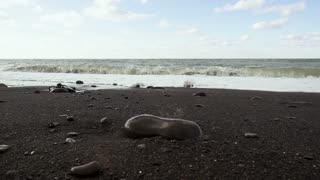 Black pebble sandy shore and foam waves with rolling waves under a cloudy bright sky slow motion