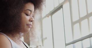 black woman with huge afro hair drinks an orange juice