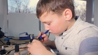 Boy assembling drone, copter in school laboratory. Steadicam. 4K.