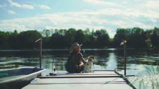 Boy sitting with his dog on landing stage at nature lake