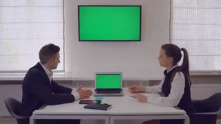Business meeting in the casual office. Caucasian woman tell about new services showing on monitor with green screen. Two people sitting at working place. Businesswoman and businessman wearing formal