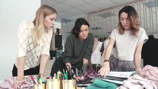 business women are engaged in creative work. fashion designers work in their small Studio. seamstresses choose fabric for a new collection of clothes