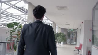 Business worker walking along the white corridor in the modern building. Confident motivated entrepreneur starting his day wearing an elegant formal suit.