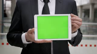 Businessman in suit holding a tablet with green screen. Man in suit showing something on the screen. Chroma key.
