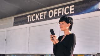 Businesswoman standing on the street near signboard ticket office using smart phone. Adult woman messaging or using application on mobile in city. Brunette with short hair wearing black dress on the