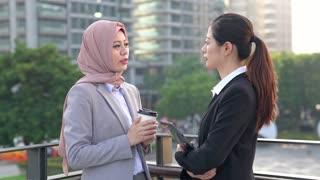 Businesswomen having a break, discussing work with Muslim colleague