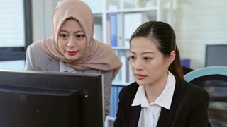 Muslim business manager working with asian woman colleague looking at computer