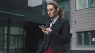 busy business woman walking down the street and reading a message from a smartphone