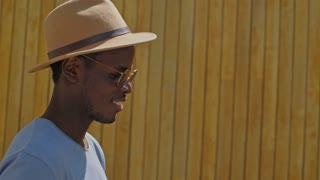 Camera follows a black trendy man, who walks in the sunshine and sun beams, slowly strolls through artisanal wooden wall, he wears a fashionable outfit