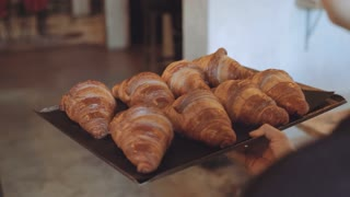 Camera follows waiter or baker carry tray full of fresh just baked crispy french croissants with butter through cafe or restaurant to table. Hospitality small business idea, local company