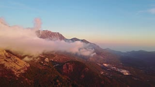 Camera moving through clouds in mountains. Fantastic dreamy sunrise on top of rocky mountain with view into misty valley
