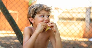 Candid Portrait Of Handsome Child Eating An Orange Outside In 4K
