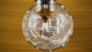 Carbonated cola from a bottle is poured into a glass with ice top view. Slow mo