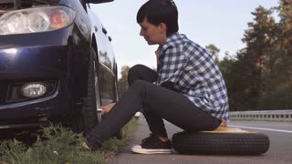 Caucasian young woman wearing casual shirt and jeans changing a tire sitting on stepney near car on the roadside. Brunette traveller outdoors