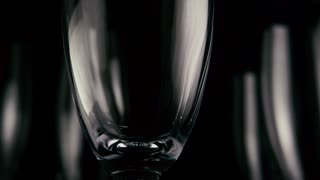 Champagne wine gently pours into a glass against a background of empty glasses black background. Slow motion