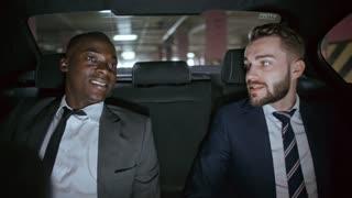 Cheerful African businessman in suit and his Caucasian colleague with beard sitting on backseat of moving car and chatting