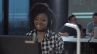 Cheerful African woman with headset in call center talking and looking at screen of desktop computer