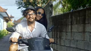 Cheerful Asian couple traveling together on scooter in Bali town and enjoying warm summer day