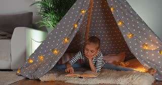 Cheerful Child Girl 9 Years Old Reading Book In Wigwam Dolly Shot
