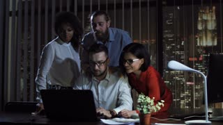 Cheerful happy multiethnic office team standing at laptop in office at night