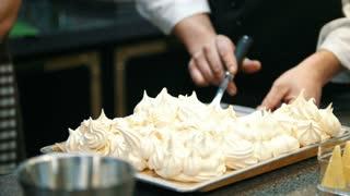 Chef putting dessert on plate - sweet Pavlova cake