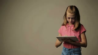 Child girl reads and touches on a tablet device