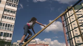 child plays on the Playground among the houses. the girl climbs to the top of the stairs.