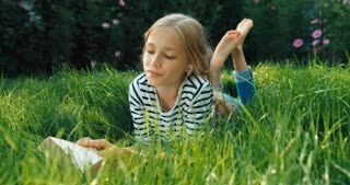Child Reading Book And Listening Music Outdoors