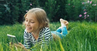 Child Using Cellphone And Lying In The Green Grass Dolly Shot