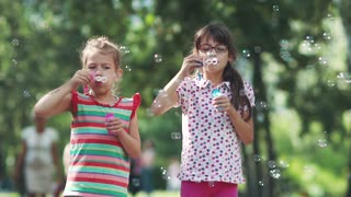 Children play in the summer park. Two little girlfriends make soap bubbles and smile. The older sister and younger sister are playing together. Slow motion