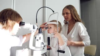 Child's ophthalmologist checks little girl's eyesight - mother and daughter in ophthalmology clinic