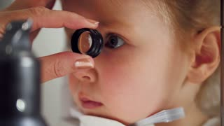 Child's ophthalmology - doctor optometrist checks eyesight for little girl