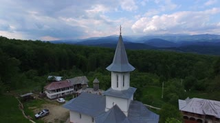 Christian church on top of green hill, aerial view, camera descending, hd video