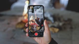 Cinemagraph, hand holds smartphone and records video of fire is burning in fireplace