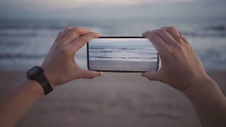 Cinemagraph of female hands hold smartphone new generation oled screen, makes photo or video for social media network, waves keep moving in loop. Inspiration to travel world