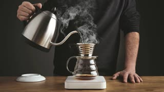 Cinemagraph of professional barista pourng not boiling water into coffee espresso french filter coffee pot, stands on scale, brewing energy caffeine drink, steam comes out