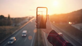 Cinemagraph of social media influencer of mobile photographer hold smartphone with high resolution screen, make video of busy evening traffic on highway in sunset. concept commuting and social media
