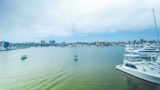 Cinematic 4K time lapse in motion (hyper lapse) on a cloudy day over a harbor bridge in Newport Beach, California with duffy boats, yachts and a small beach area