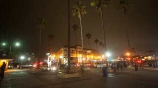 Cinematic 4K time lapse in motion (hyper lapse) shot at night in front of the Newport Beach pier entrance with the Ben Carlson lifeguard statue, palm trees and city lights.